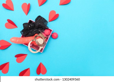 Symbols of love for Happy Women's, Valentine's Day. Flat lay. Paper elements in the shape of a heart on a blue background and a gift for a girl with underwear, toys for adults a dildo, vaginal balls.