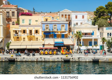 SYMI, GREECE - September 6,2015: View of a coastline street and fishing boats moored in Yialos harbour on Symi island,Greece. Symi is easy and popular destination for day tripping from Rhodes island.