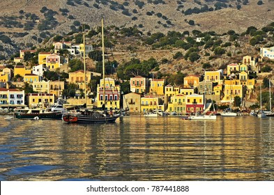 Symi island Dodecanese, Greece. August 5, 2014. Sunset seascape with panoramic view of the traditional houses and the port with the sailing boats in Symi island Dodecanese, Greece.