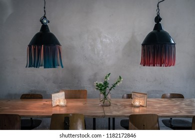 Symmetric lampshades in Berlin cafe with table.