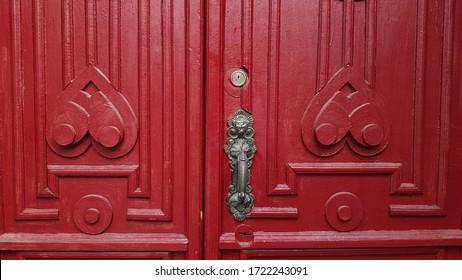 Symmetric pattern frames of red double door panels of antique door with sculptural vintage door handle. Red painted ornate wooden door details