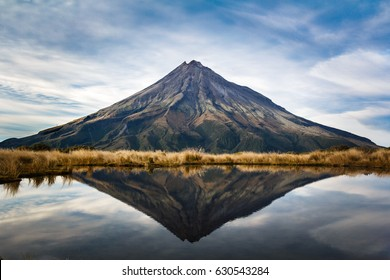 A symmetric picture of the taranaki volcano in the north island of new zealand and with the reflection of tho mountain and the climber in a lake