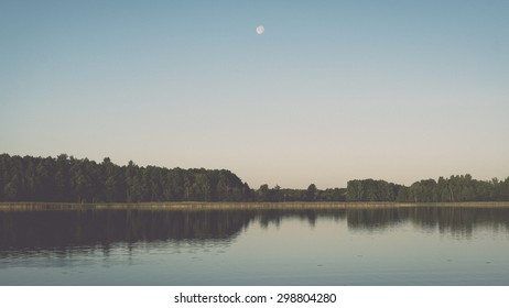 symmetric reflections on calm lake water with forests and islands - retro vintage effect