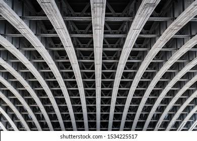 Symmetric steel framework under a bridge over the river Thames in London.