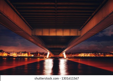 Symmetric underside of the bridge at night view with warm color tones and long exposure water. Köln, Cologne in Germany