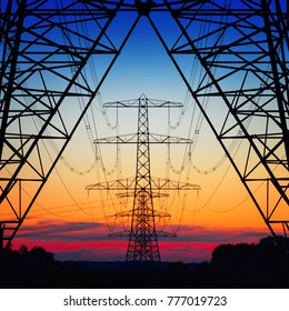 symmetric view of power pylons against a beautiful coloured evening sky