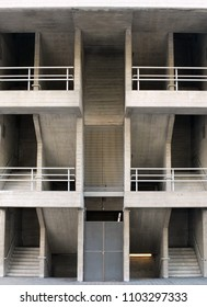 symmetrical angular brutalist concrete stairways with multiple floors and railings in a large modern building