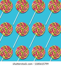Symmetrical arrangement of lollipop candies on turquoise background, colorful sweet food texture