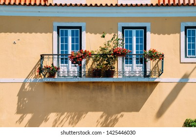 Symmetrical balcony with flowers with yellow paint facade.