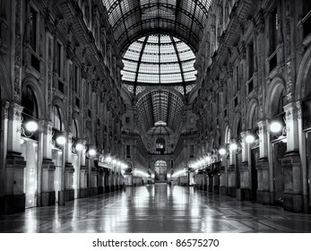 Symmetrical black and white night shot of the hall of the landmark arcade or covered mall, Galleria Vittorio Emanuele II in Milan, Italy