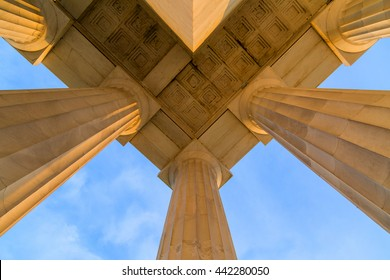 Symmetrical Ceiling at Top Corner of Lincoln Memorial Roof during early morning DC Sunrise. The Columns and marble are lit by the sun and cast shadows. The composition utilizes symmetry.