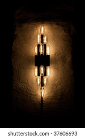 A symmetrical cluster of candle-shaped light bulbs.