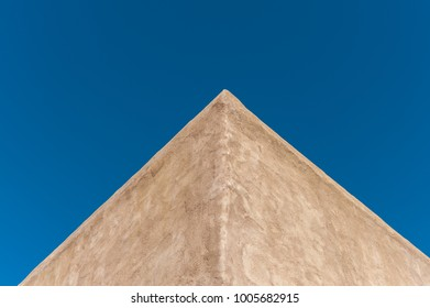 Symmetrical corner of adobe building in the American Southwest against a cloudless,  sunny, blue sky. Adobe was a traditional building material used by Native Americans suited to dry, arid climates.