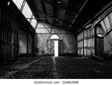 Symmetrical image of an abandoned barn near the Antwerp harbor, with the door standing open exactly in the middle leading the light beams into the barn