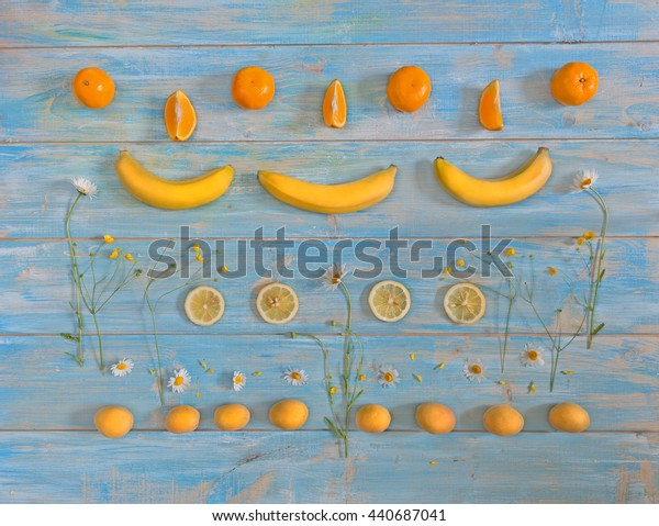 Symmetrical pattern of yellow and orange fruits and wild flowers lying on  wooden table painted in blue color.