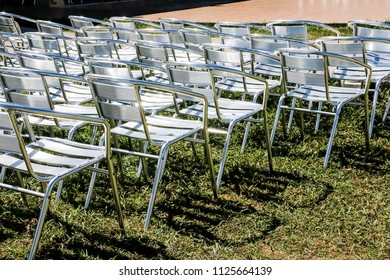 Symmetrical rows of silver folding chairs Ready for party or representation, presentation. metallic chairs in hotel area prepped for performance, animation program