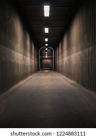 symmetrical shot of an empty dark hallway in a factory with neon lights shining