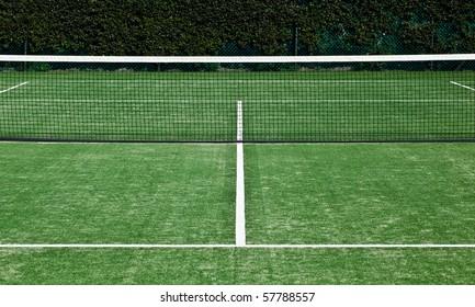 Symmetrical shot of tennis net and forecourt.