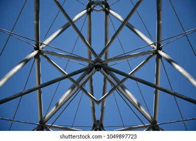 Symmetrical steel structure with supporting tension cables against blue sky.