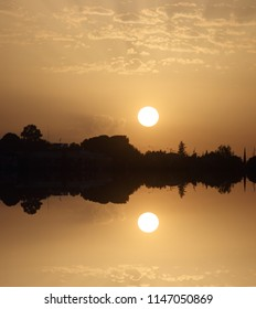 symmetrical sunset photograph reflected in a lake,Sunrise with reflected sun, peace, calm, serenity, harmony, fullness, well-being, nature, natural, contemplate, meditate, breathe, grow,happiness,