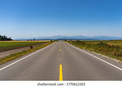 Symmetrical view down a two-lane road, flat landscape with fields either side and big blue sky and the sea at the end. Coupeville, Whidbey Island, Washington, USA
