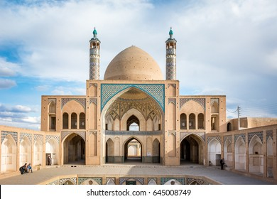 A symmetrical view of the mosaic work and sandstone colored Islamic architecture of the Agha Bozorg mosque in the desert city of Kashan, Iran, during the sunset golden hour