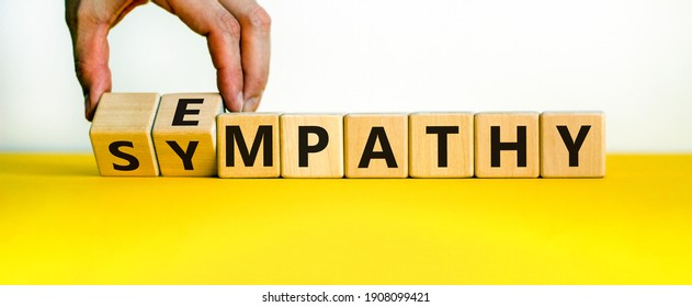Sympathy or empathy symbol. Businessman turns wooden cubes and changes the word 'empathy' to 'sympathy'. Beautiful white background. Copy space. Psychological, sympathy or empathy concept.