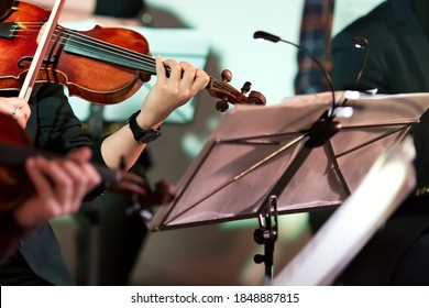 Symphony music. Woman playing the violin in orchestra near music note stand