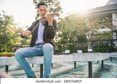 Symphony orchestra on outdoor background, hands playing violin. Male violinist playing classical music on violin. Talented violinist and classical music player solo performance.