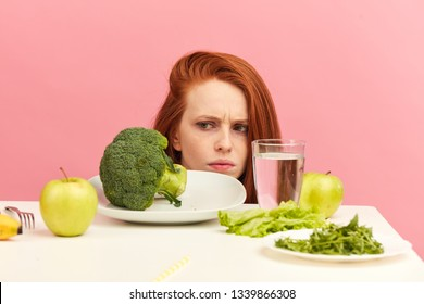Symptoms of anorexia manifested in aversion to food. Portrait of grimacing unsatisfied facial emotional expression lady refusing to eat fresh green salad in bowl on table in light room