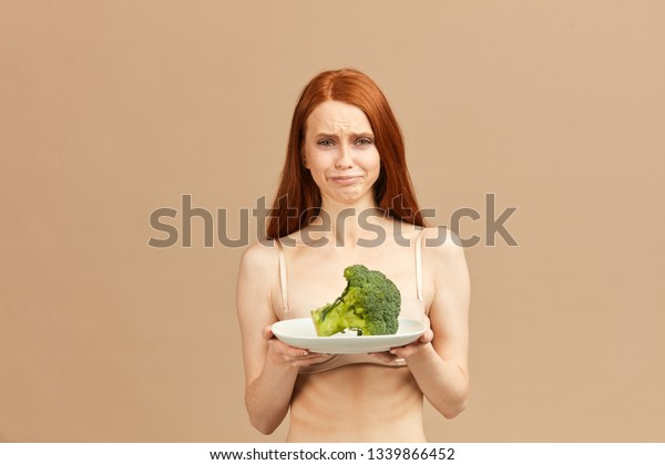 Symptoms of anorexia manifested in disgust for food. Portrait of grimacing unsatisfied facial emotional expression young woman refusing to eat fresh broccoli on plate, posing over pink background