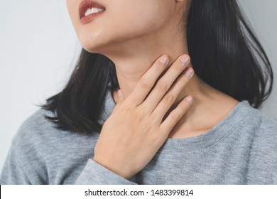 Symptoms from flu season in winter concepts. Close up woman touching her neck and suffering from sore throat.