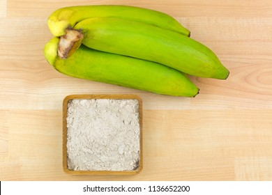 Synbiotic dried banana fruit powder made of organic whole Gros Michel banana, known as Big Mike, top view on wooden background