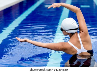 Synchronized female swimmer in the pool stretching