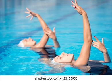 Synchronized swimming duet performing in swimming pool
