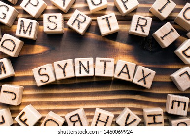 syntax  composed of wooden cubes with letters, grammatical arrangement of words in a sentence concept, the random letters around, top view on wooden background