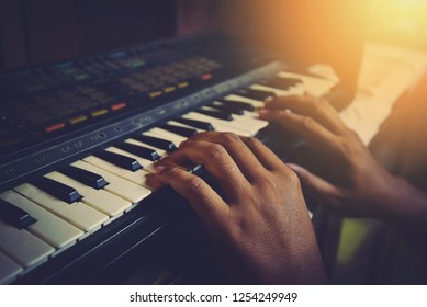 Synthesizer piano player musician hands playing different chords on old piano keys on dark background vintage style / MIDI keyboard electronic