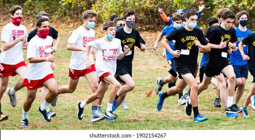 Syosset, New York, USA - 1 November 2020: Youn high school boys at the start of a cross country running race during the cornavirus pandemic.