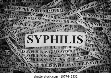 Syphilis. Torn pieces of paper with the words Syphilis. Concept Image. Black and White. Closeup.