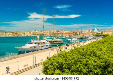Syracuse - April 2019, Sicily, Italy: Cityscape of Syracuse viewed from Ortygia. View of an embankment with walking people, turquoise water, yachts and touristic ships