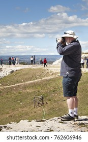 SYRACUSE, ITALY. April 3, 2015: A tourist with a binoculars looks down on the ruins of the Roman amphitheater of Syracuse in Sicily, Italy. Behind him, more distant, more tourists visiting.