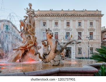 Syracuse / Italy - December 28 2018: The Fountain of Diana in Piazza Archimede, with neoclassical buildings in the background.