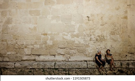 Syracuse, Italy - June 29 2017: Two old ladies in the night street of the famous historic town Syracuse, Sicily.