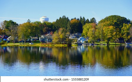 Syracuse, New York, U.S.A - October 22, 2019 - The view of the waterfront homes near Oneida Lake surrounded by the stunning colors of fall foliage