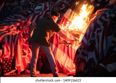 Syracuse, New York/USA - May 26,2019: A veteran lights a bonfire of american flags at the Watch Fire Ceremony .