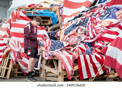 Syracuse, New York/USA - May 26,2019: A Teenager places an american flag on the pile at the Syracuse, New York Watch Fire to properly retire the flag.
