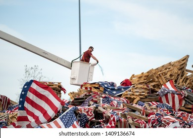 Syracuse, New York/USA - May 26,2019: A man pours gasoline over a Large pile of American Flags in preperation for a flag retirement ceremony.