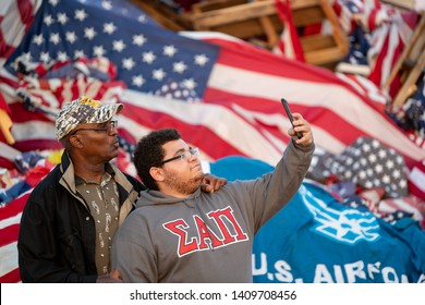 Syracuse, New York/USA - May 26,2019: Two African American men take a selfie in front of a pile of american flags at the watch fire ceremony.