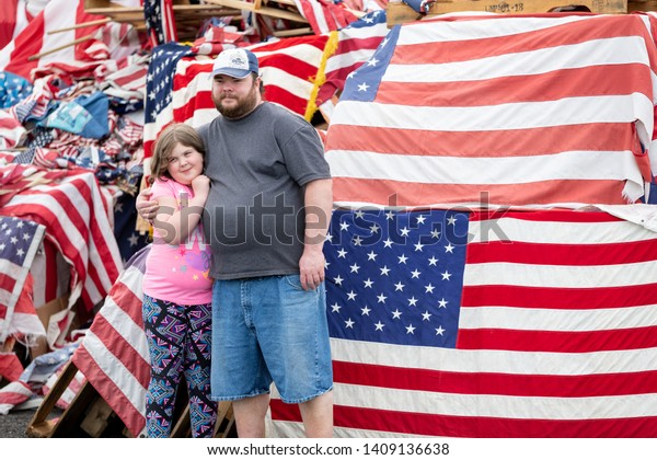 Syracuse, New York/USA - May 26,2019: A Father and Daughter pose in front of a pile of american flags at the watch fire ceremony in Syracuse, New York.