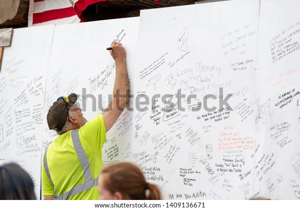Syracuse, New York/USA - May 26,2019: A Veteran signs a wall to remember veterans that have passed away in service to their country.